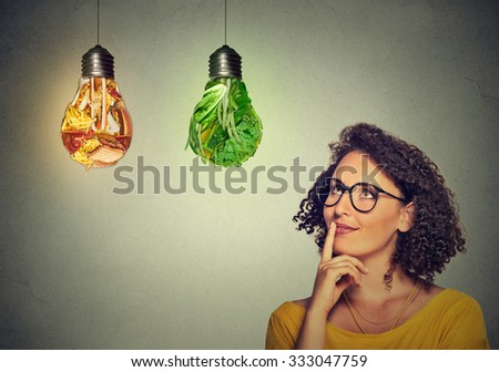 Portrait beautiful woman thinking looking up at junk food and green vegetables shaped as light bulb isolated on gray background. Diet choice right nutrition healthy lifestyle wellness concept - stock photo