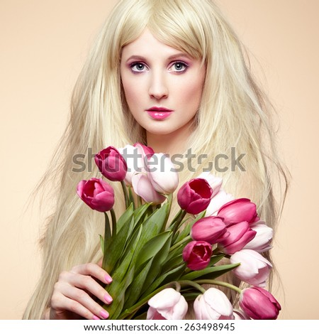 Portrait beautiful woman with bouquet of flowers. Tulips. Blonde girl. March 8 - stock photo