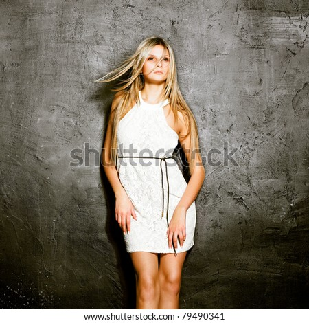 Portrait beautiful woman with elegant white dress on grunge wall background. Fashion photo - stock photo