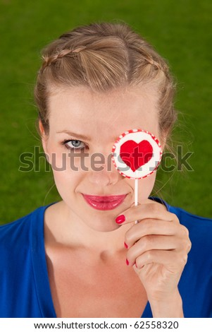 Portrait beautiful young blond girl with lollipop heart in her hand - stock photo