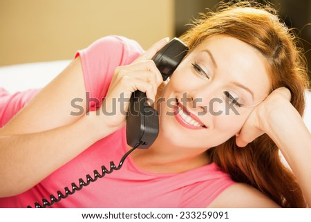 Portrait beautiful young happy woman talking on a phone lying in bed making hotel room service oder. Positive human face expression emotion feeling. Communication, leisure, travel concept - stock photo