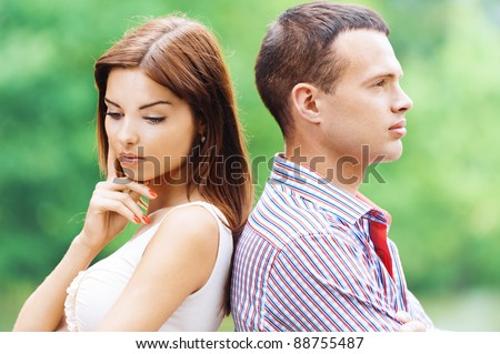 portrait beautiful young man woman couple standing back each other sad background summer green park