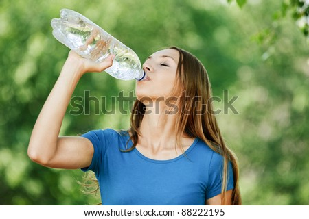 portrait beautiful young woman background green summer park drinking bottle - stock photo