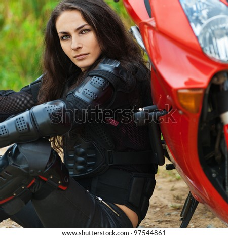 portrait beautiful young woman pensive sitting leather jacket leaning motorcycle - stock photo