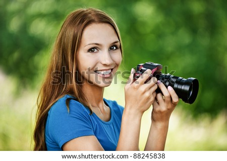portrait beautiful young woman smiling holding camera background summer green park - stock photo
