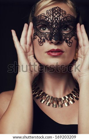 Portrait blond woman in mask against dark