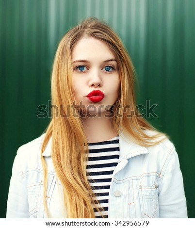 Portrait blonde young girl with red lipstick blowing lips - stock photo