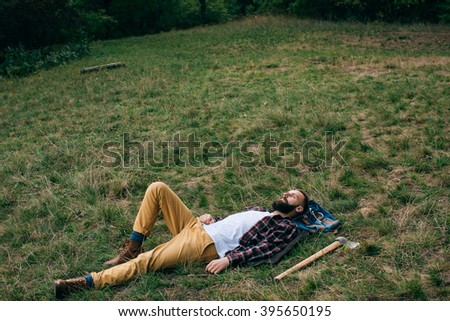 Portrait brutal bearded and moustached woodcutter hipster Gypsy man in the forest with ax. Man lying on the grass and dreams