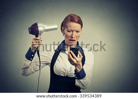 Portrait business woman deal maker reading bad news on smartphone looking at mobile phone holding hairdryer isolated on grey background. Human face expression emotion. Busy life of corporate executive - stock photo