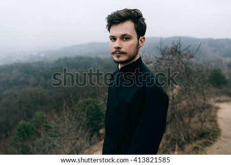 Portrait  catholic bearded priest or pastor posing outdoors in mountains - stock photo