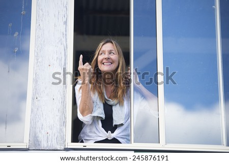 Portrait cheeky attractive mature woman pointing with finger up, inviting or warning with a happy smile while standing at window, copy space. - stock photo