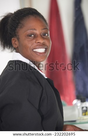 Portrait cheerful beautiful African girl in house cleaning uniform - stock photo