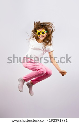 Portrait cheerful, happy, cute, excited, joyful little girl with summer sunglasses, jumping against colored grey background. Positive human emotions, expressions, reaction, life perception, feelings - stock photo