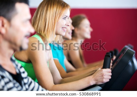 Portrait cheerful people training on exercise bikes together in gym