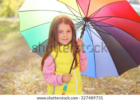 Portrait child with colorful umbrella in sunny autumn day