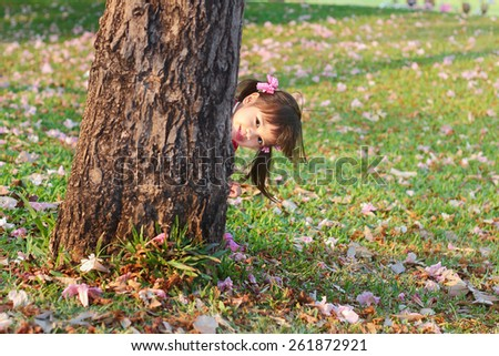 Portrait children, Little asian girl in pink qipao was smiling and playing hide-and-seek in the park - stock photo