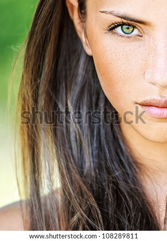 Portrait close up half of face young beautiful woman, on green background summer nature.