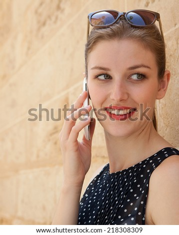 Portrait close up of a beautiful young professional businesswoman using a smart phone technology to make a phone call while leaning on a textured stone wall in a financial city. Lifestyle outdoors. - stock photo