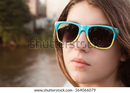 Portrait close up of a pretty teenage girl in sunglasses outdoor. Toned effect - stock photo