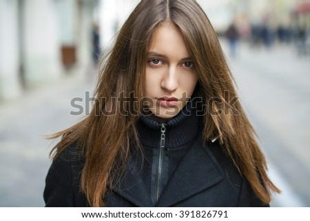 Portrait close up of young beautiful brunette woman in black coat, on spring street background