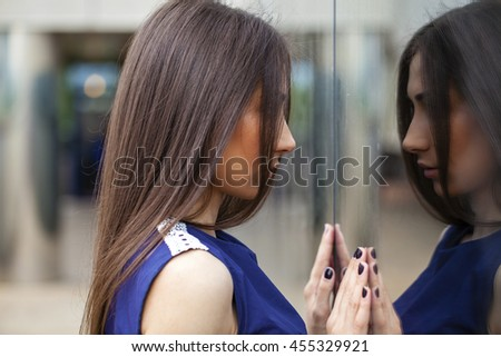 Portrait close up of young beautiful brunette woman in blue dress posing near mirrored wall - stock photo