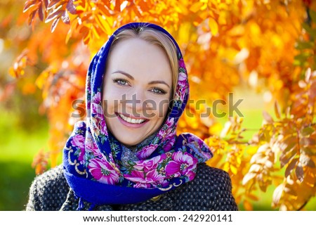 Portrait close up of young beautiful woman, on background autumn park - stock photo