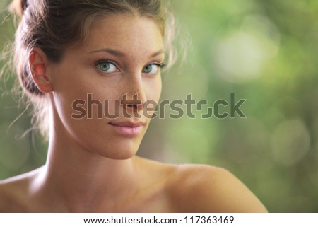 Portrait close up of young beautiful woman, on green background