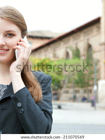 Portrait close up view of an attractive smiling young professional businesswoman using smartphone to make a phone call in a classic city, outdoors. (Business, People, Technology) - stock photo