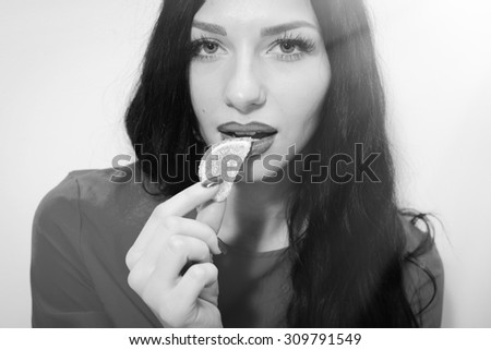 Portrait closeup of beautiful luxury sensual lady with seductive lips, white excellent teeth and manicured nails eating jujube or candy. Black and white photography - stock photo