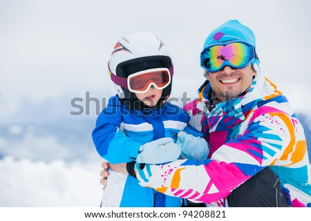 portrait closeup of happy and smiling father and son in ski goggles and a helmet - stock photo