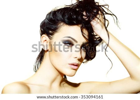 Portrait closeup of one attractive young sensual cool sexy woman holding long curly hair with hand has bright makeup standing indoor looking forward, horizontal picture - stock photo