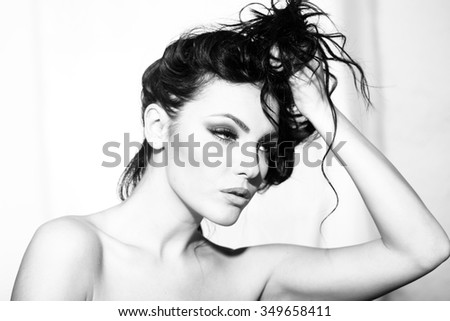 Portrait closeup of one pretty young sensual elegant sexy woman holding long curly hair with hand has bright makeup standing indoor looking forward black and white, horizontal picture