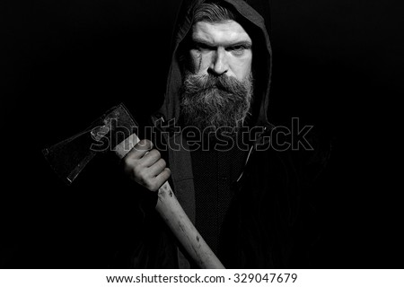 Portrait closeup view of one senior hunter man in hood with spooky painted face of zombi and long white lush beard holding axe black and white, horizontal picture