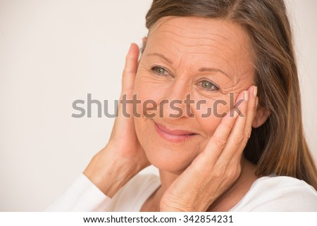 Portrait confident relaxed retired mature woman posing happy smiling with hands on face, isolated, bright background. - stock photo