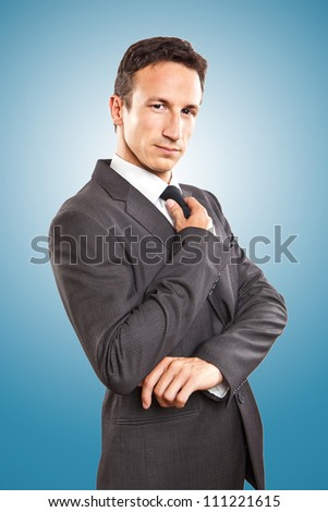 Portrait cool young businessman on blue background