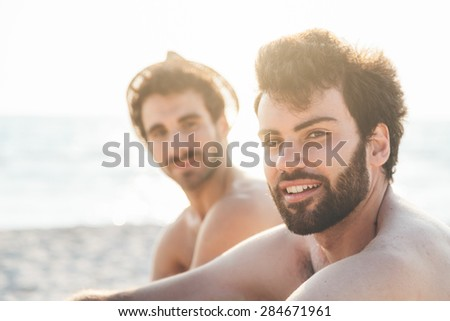 Portrait. Couple of friends at sunset on the beach on a day of rest summer vacation together, after spending a day of relaxation and fun - stock photo