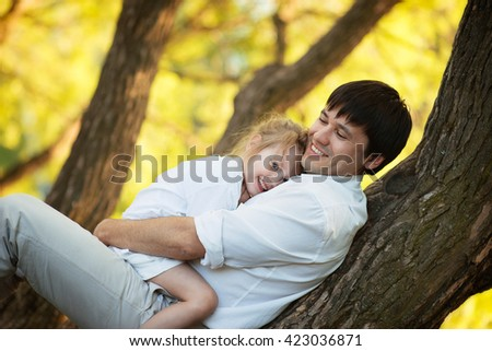 portrait dad and daughter sitting on a tree and laughing in the summer garden, happy family - stock photo