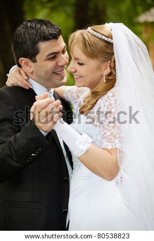 Portrait dancing wedding couple at a park on a sunny day - stock photo
