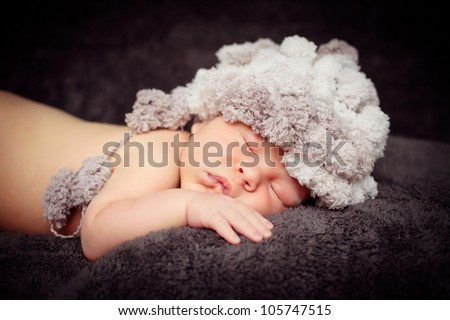 Portrait 0-7 days .A newborn baby is wearing a gray hat and laying down sleeping on a soft black background. Soft focus, shallow DoF.