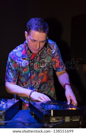 Portrait DJ turns the records at the club - stock photo