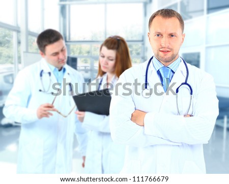 Portrait doctor smiling with colleagues in background - stock photo