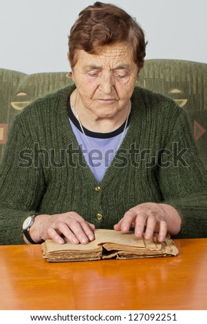 Portrait elderly woman reading old  book - stock photo