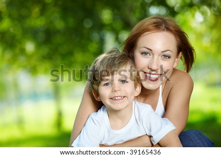 Portrait - embraces of mother with the small son against a summer garden - stock photo