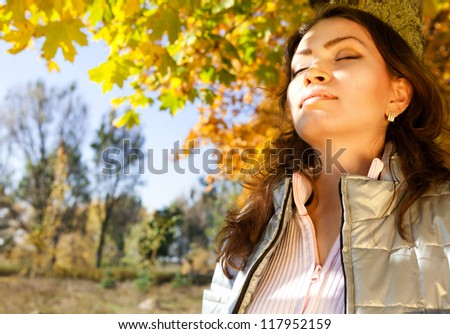 Portrait enjoyed beautiful asian girl at the autumn park - stock photo