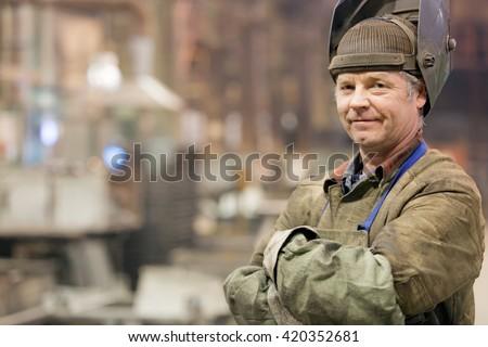 Portrait factory senior welder worker on manufacture workshop background - stock photo