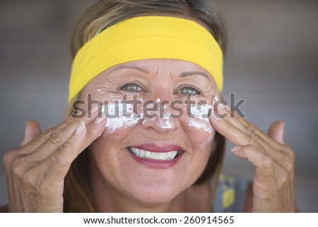 Portrait fit active attractive mature woman with protective sunscreen skin care creme and moisturiser lotion on joyful smiling face, yellow headband, blurred background. - stock photo