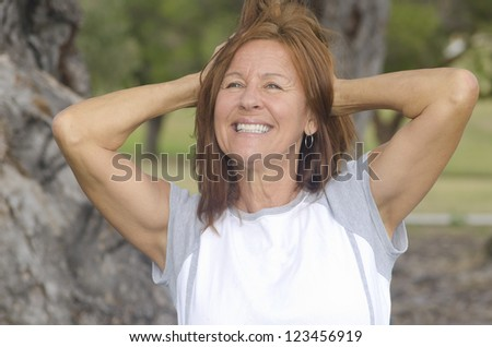 Portrait fit and healthy, confident and happy attractive middle aged woman with arms up, with blurred background outdoor. - stock photo