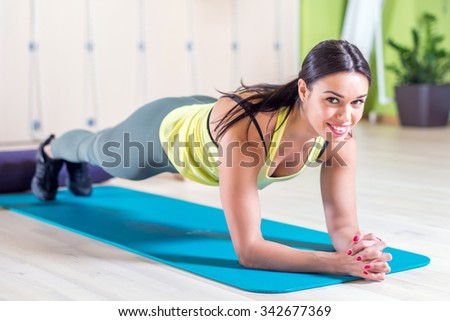 portrait fitness training athletic sporty woman doing plank exercise in gym or yoga class concept exercising workout aerobic. - stock photo