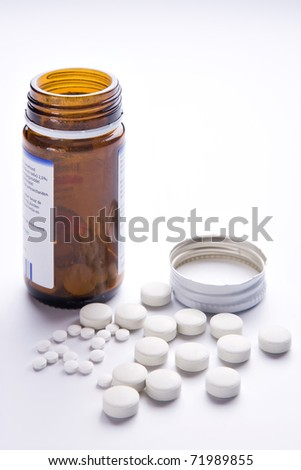 Portrait-frame of a collection of common, white, disk-shaped pills, with a brown jar and lid.
