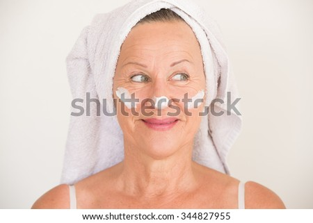Portrait friendly attractive mature woman with towel and protective skin care creme and moisturizer lotion on happy smiling face, bright background. - stock photo